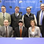 Cody Triolo, surrounded by his parents and Princeton Day School staff, signs a letter of intent to play lacrosse at Lehigh University. Pictured are (front) Triolo's father, Christopher, Triolo,and his mother,Kris Triolo (back) Head of School Paul Stellato, Director of Athletics Tim Williams, Lacrosse Coach Rob Tuckman, and Head of Upper School Carlton Tucker.