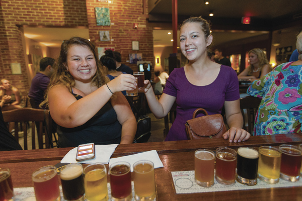'Brewing aficionados' at the bar: Carol Petrosyan of Ewing, left, and Jamie Williams of Boston with a seven-beer flight of Triumph's own brews. (Photo by Suzette J. Lucas.)