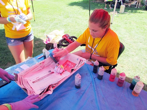 Camper applies tie-dye to a backpack banded by volunteers at ERA Central Realty.